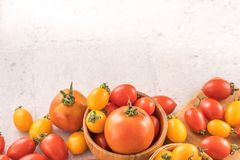 Fresh yellow and red cherry tomatoes in a basket on a cement board, close up, copy space, top view. Fresh yellow and red cherry tomato in a basket on a cement stock image