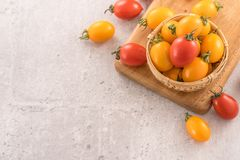 Fresh yellow and red cherry tomatoes in a basket on a cement board, close up, copy space, top view. Fresh yellow and red cherry tomatoes in a basket on a cement stock image
