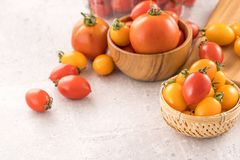 Fresh yellow and red cherry tomatoes in a basket on a cement board, close up, copy space, top view stock photo
