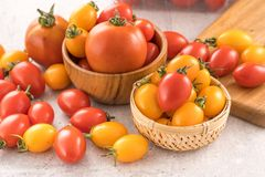 Fresh yellow and red cherry tomatoes in a basket on a cement board, close up, copy space, top view. Fresh yellow and red cherry tomatoes in a basket on a cement royalty free stock images