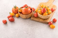 Fresh yellow and red cherry tomatoes in a basket on a cement board, close up, copy space, top view. Fresh yellow and red cherry tomatoes in a basket on a cement royalty free stock image
