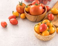 Fresh yellow and red cherry tomatoes in a basket on a cement board, close up, copy space, top view. Fresh yellow and red cherry tomatoes in a basket on a cement royalty free stock photography