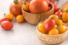 Fresh yellow and red cherry tomatoes in a basket on a cement board, close up, copy space, top view. Fresh yellow and red cherry tomatoes in a basket on a cement stock photos