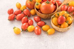 Fresh yellow and red cherry tomatoes in a basket on a cement board, close up, copy space, top view. Fresh yellow and red cherry tomatoes in a basket on a cement stock images