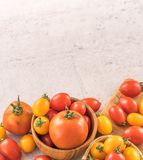 Fresh yellow and red cherry tomatoes in a basket on a cement board, close up, copy space, top view. Fresh yellow and red cherry tomatoes in a basket on a cement stock photography