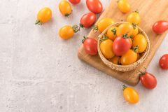 Fresh yellow and red cherry tomatoes in a basket on a cement board, close up, copy space, top view. Fresh yellow and red cherry tomatoes in a basket on a cement royalty free stock photo
