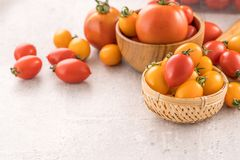 Fresh yellow and red cherry tomatoes in a basket on a cement board, close up, copy space, top view. Fresh yellow and red cherry tomatoes in a basket on a cement stock photo