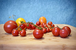 Fresh yellow and red cherry tomatoes on the wooden board. And blue background, Selective Soft focus Royalty Free Stock Photos