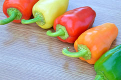 Fresh yellow, red and green bell peppers  on wood Stock Photos