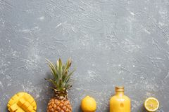 Fresh yellow smoothie with pineapple, mango and lemons on gray table, top view. With copy space Royalty Free Stock Images