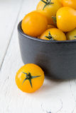 Fresh yellow tomatoes on white wooden table Stock Image