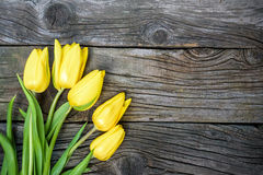 Fresh yellow tulip flowers with towel on ancient vintage wooden table. Stock Photos