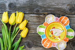 Fresh yellow tulip flowers with towel on ancient vintage wooden table  plates. Stock Photos
