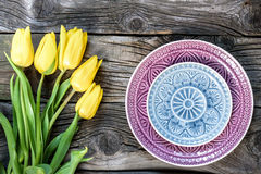 Fresh yellow tulip flowers with towel on ancient vintage wooden table  plates. Stock Photography