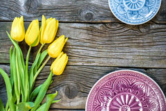 Fresh yellow tulip flowers with towel on ancient vintage wooden table  plates. Stock Photo