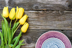 Fresh yellow tulip flowers with towel on ancient vintage wooden table  plates. Stock Image