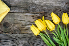 Fresh yellow tulip flowers with towel on ancient vintage wooden table. Stock Photography