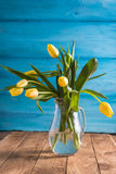 Fresh yellow tulips in vase on wooden background Stock Photography