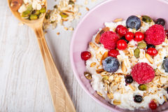 Fresh yoghurt with home made cereals. And muesli, fresh raspberry and blueberry on wooden textured background as healthy breakfast stock photo