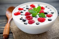 Raspberry and green mint. Fresh yoghurt with raspberry and green mint on wooden table. sweet dessert food Stock Image