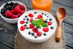 Raspberry and green mint. Fresh yoghurt with raspberry and green mint on wooden table. sweet dessert food Stock Photos