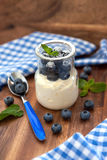 Fresh yogurt with blueberry and mint in a glass jar Royalty Free Stock Photos