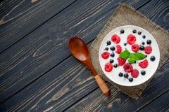 Raspberry and green mint. Fresh yogurt with raspberry and green mint on wooden table. sweet dessert food Stock Photos