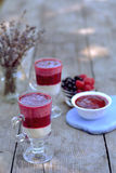 Fresh yogurt with sweet, juicy raspberry and blackcurrant in glass on foreground. Tasty breakfast Royalty Free Stock Photography