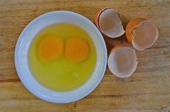 Fresh yolk and albumen with opened shells. In white ceramic dish Stock Photo