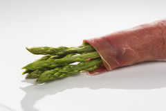 Fresh Young Asparagus Wrapped in Prosciutto. On the white background Stock Images