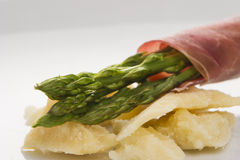 Fresh Young Asparagus Wrapped in Prosciutto Meat. On cheese well decorated on white plate Royalty Free Stock Photography