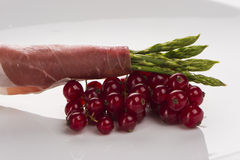 Fresh Young Asparagus Wrapped in Prosciutto Meat o. N currants on white plate Royalty Free Stock Photography