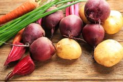 Fresh young beets and potatoes with carrots. On table Royalty Free Stock Photos