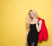Fresh young blond woman smiling. Portrait of a fresh young blond woman smiling on yellow background Stock Photography