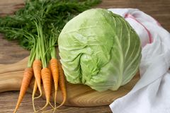 Fresh young cabbage and carrots with greens for coleslaw salad. On a wooden board on a wooden table, selective focus. Healthy diet food royalty free stock photo