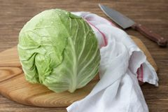 Fresh young cabbage on wooden board on wooden table. Selective focus Stock Photos