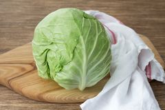Fresh young cabbage on wooden board on wooden table. Selective focus Stock Image