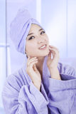 Fresh young girl after bath. Fresh young girl wearing a bathrobe and towel after bath, smiling at camera on the bathroom Royalty Free Stock Images