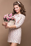 Fresh young girl, light silk dress, smile, retro curls pin-up style with basket of flowers. Beauty face , body. Royalty Free Stock Photo