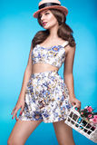 Fresh young girl in summer dress, smile, retro hat pin-up style with basket of flowers. Beauty face , body. Stock Photography