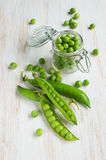 Fresh young green peas. On white wooden table Stock Image