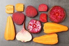 Fresh young sliced beets and carrots. On grey background royalty free stock photo