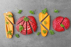 Fresh young sliced beets and carrots with parsley. On grey background stock images