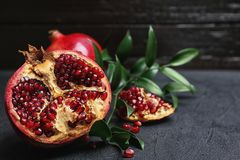 Fresh yummy pomegranate. On dark table Stock Images