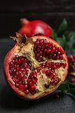 Fresh yummy pomegranate. On dark table Stock Photos