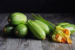 Fresh Zucchini and Zucchini Blossoms. Zucchini and Zucchini Blossoms. Fresh green zucchini with flowers on rustic background stock photo