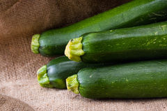 Fresh zucchini. Close up of fresh zucchini or green squash with a burlap sac as a background stock images