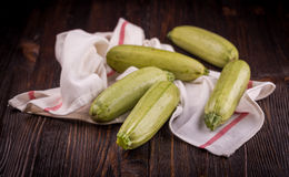 Fresh zucchini on wooden table. Some fresh zucchini courgettes on a dark wooden background Stock Images