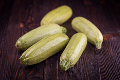 Fresh zucchini on wooden table. Some fresh zucchini courgettes on a dark wooden background Royalty Free Stock Image