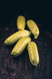 Fresh zucchini on wooden table. Some fresh zucchini courgettes on a dark wooden background Stock Photos